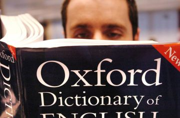 мужчина читает книгу оксфордский словарь новое издание